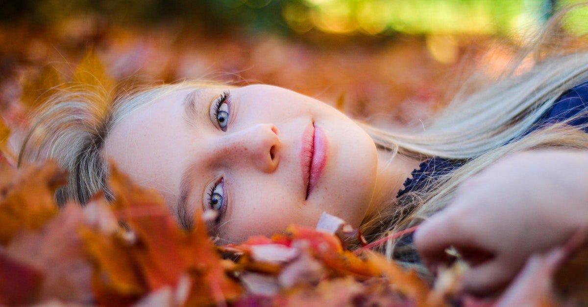 donna distesa tra foglie autunnali