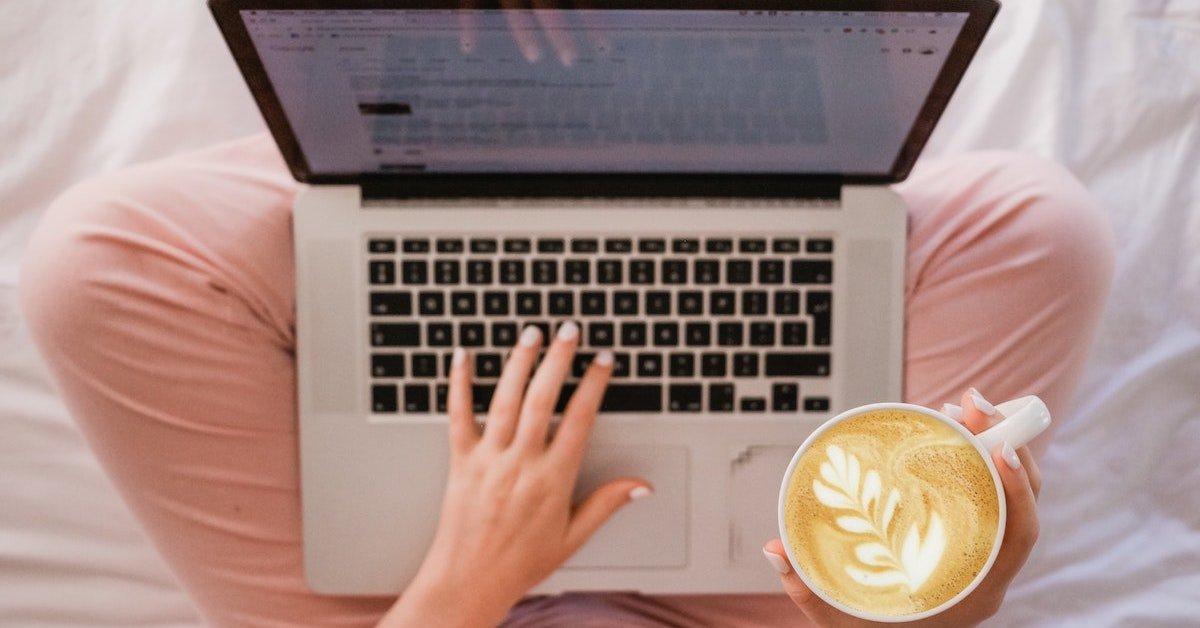 vista dall'alto di donna a gambe incrociate con mackbook e tazza di cappuccino