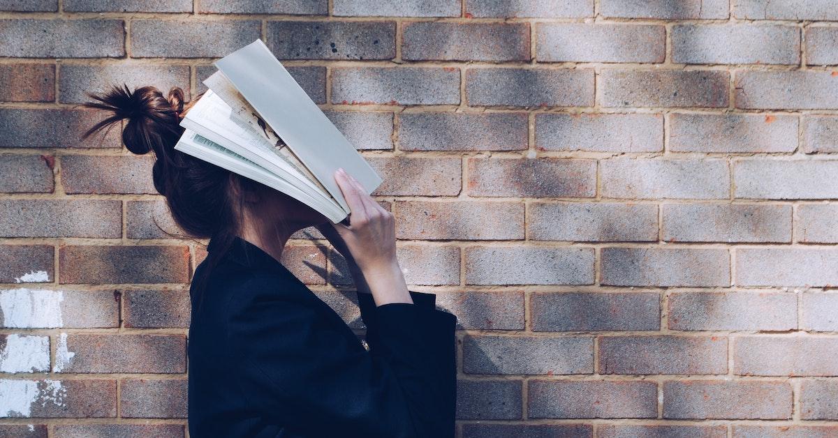 donna col volto coperto da un giornale